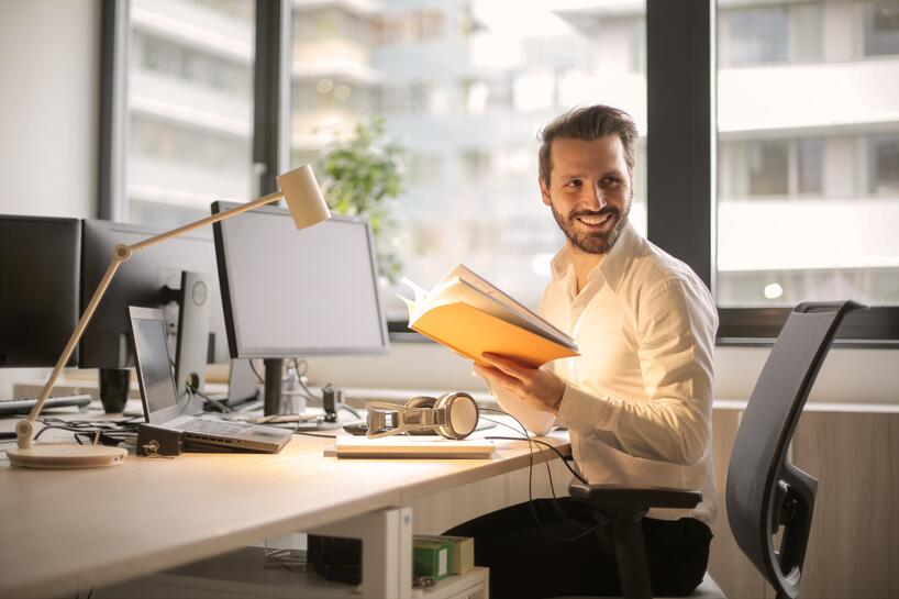 An accommodation case manager happily reads Presagia's new ADA whitepaper at his desk